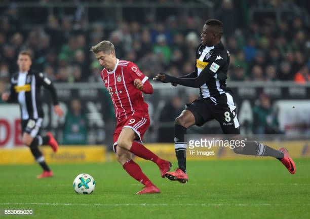 Denis Zakaria of Borussia Moenchengladbach and Robert Lewandowski of Bayern Muenchen battle for the ball during the Bundesliga match between Borussia...