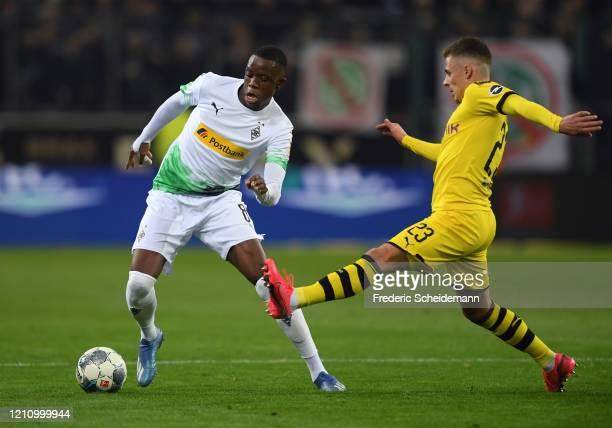 Denis Zakaria of Borussia Moenchengladbach battles for possession with Thorgan Hazard of Borussia Dortmund during the Bundesliga match between...