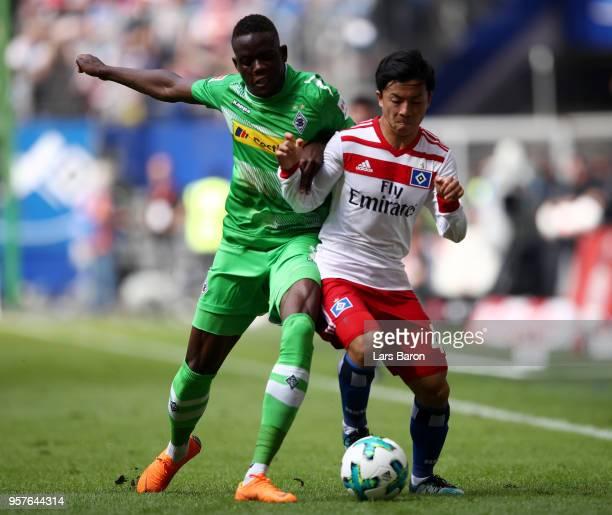 Denis Zakaria of Borussia Moenchengladbach battles for possession with Tatsuya Ito of Hamburger SV during the Bundesliga match between Hamburger SV...