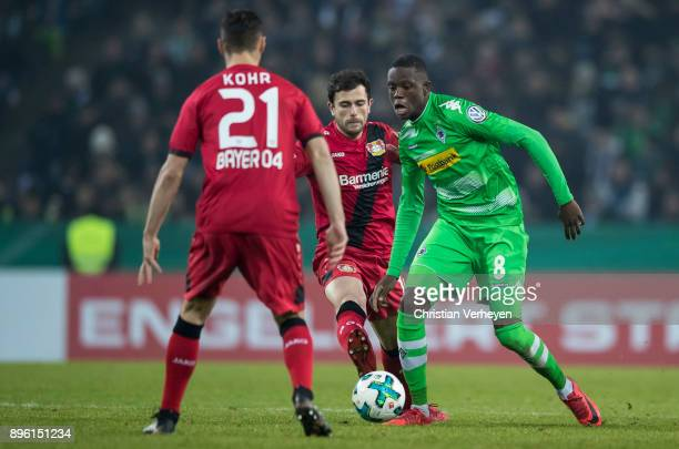 Denis Zakaria of Borussia Moenchengladbach Dominik Kohr and Admir Mehmedi of Bayer 04 Leverkusen battle for the ball during the DFBCup match between...
