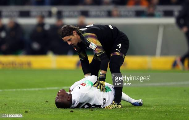 Denis Zakaria of Borussia Moenchengladbach is helped by Yann Sommer of Borussia Moenchengladbach after picking up an injury during the Bundesliga...