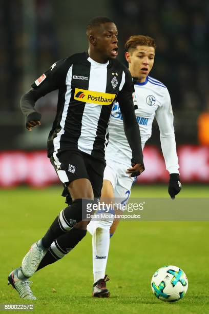 Denis Zakaria of Borussia Monchengladbach gets past the tackle from Amine Harit of Schalke 04 during the Bundesliga match between Borussia...