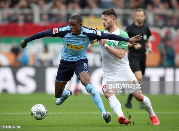 Denis Zakaria of Borussia Monchengladbach holds off Eduard Lowen of Augsburg during the Bundesliga match between TSG 1899 Hoffenheim and FC Bayern...