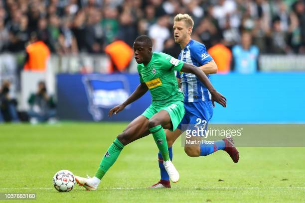Denis Zakaria of Borussia Monchengladbach is challenged by Arne Maier of Hertha BSC during the Bundesliga match between Hertha BSC and Borussia...