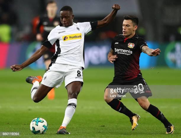 Denis Zakaria of Moenchengladbach is chased by Aranguiz of Bayer Leverkusen during the Bundesliga match between Bayer 04 Leverkusen and Borussia...