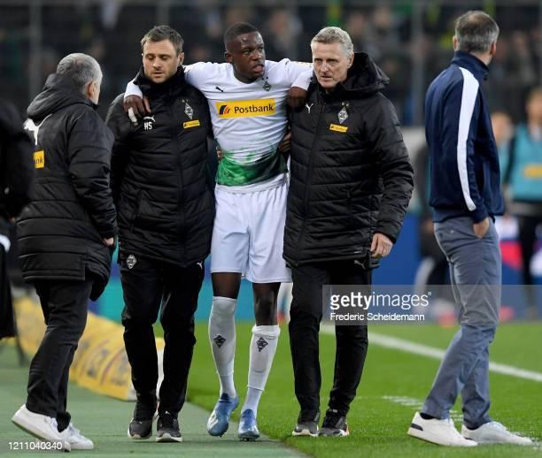 Denis Zakaria of Moenchengladbach leaves the field injured during the Bundesliga match between Borussia Moenchengladbach and Borussia Dortmund at...