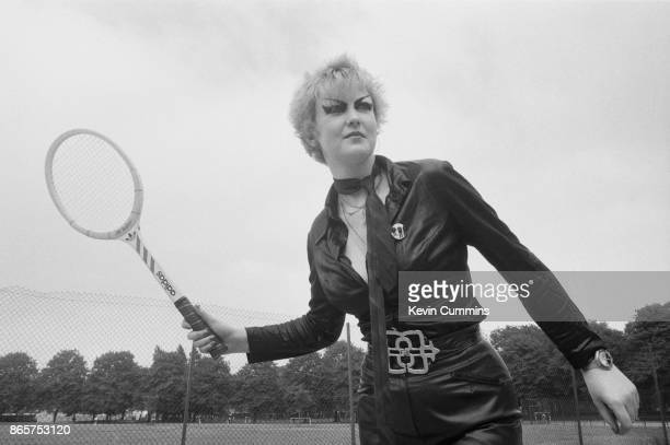 Denise a punk wearing a leather jumpsuit and heavy eyeliner playing tennis outdoors 1977