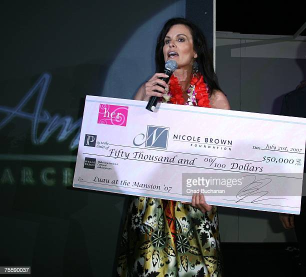 Denise Brown holds a donations check at the HER Luau at The Playboy Mansion on July 21 2007 in Holmby Hills California