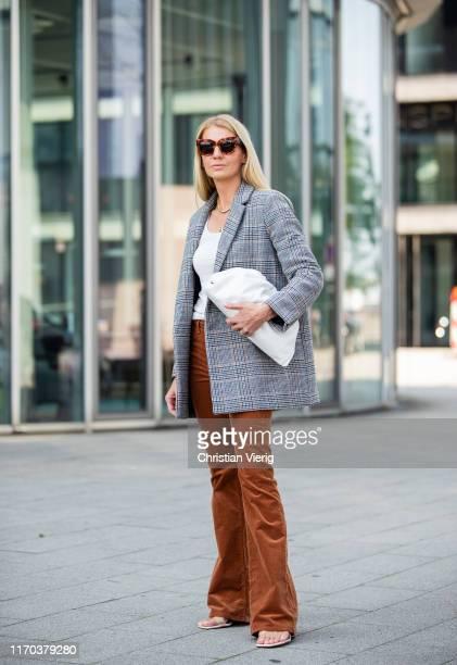 Denise Buschkühle is seen wearing grey plaid blazer Samsoe Samsoe, rusty flared pants Veronica Beard, ATM top, Bottega Veneta bag, Zara sandals,...