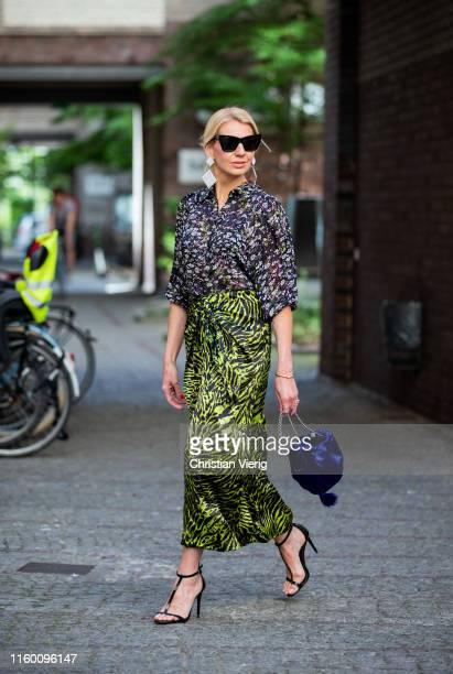 Denise Buschkühle is seen wearing top and skirt with print Ganni, black Rachel Zoe heels, blue Mango bag, Alessandra Rich earrings during Berlin...
