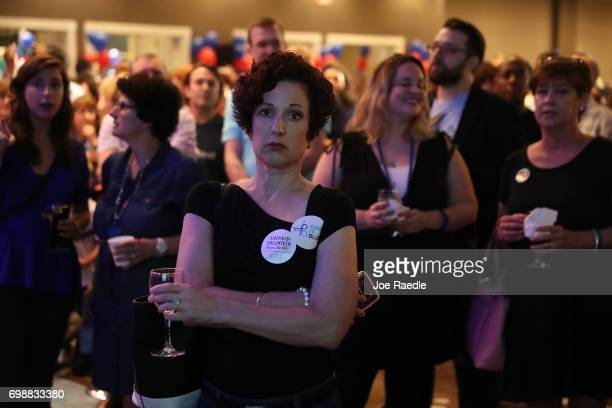 Denise Garner watches election results come in on a television screen setup at the election party for Democratic candidate Jon Ossoff being held at...
