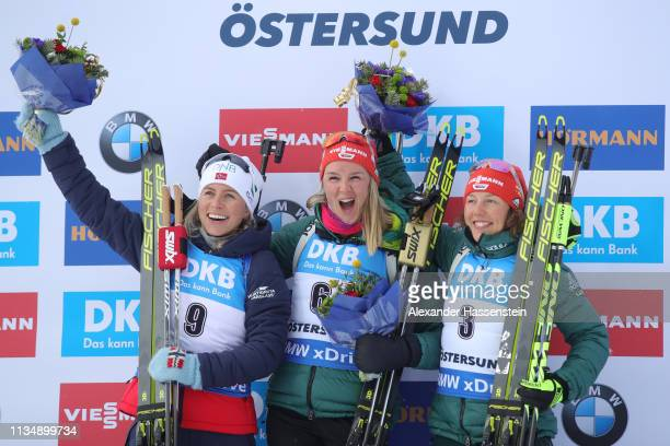 Denise Herrmann of Germany celebrates winning the gold medal ahead of Tiril Eckhoff of Norway and Laura Dahlmeier of Germany during the flower...