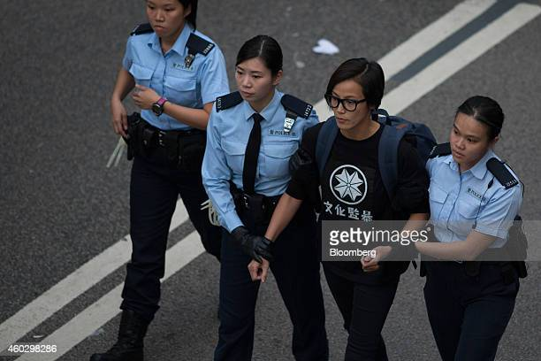 Denise Ho Wan-see, also known as HOCC, a singer, is escorted by police officers near the Central Government Offices in the Admiralty district of Hong...