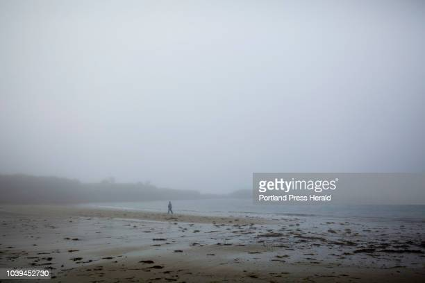 Denise Leboeuf of Worcester Mass walks along the beach on a foggy morning at Kettle Cove Monday September 17 2018 Leboeuf said that foggy days are...
