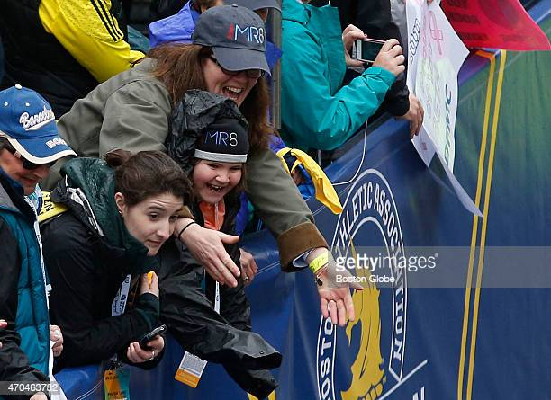Denise Richard and her daughter Jane cheer on a team MR8 runner as they cross the Boston Marathon finish line on April 20 2015