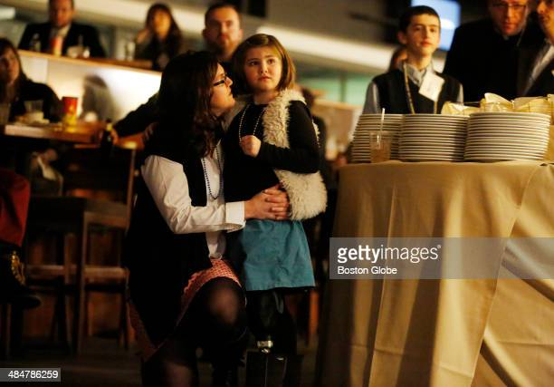 Denise Richard comforts her daughter Jane Richard as a video showing images of of the 2013 Boston Marathon race before the bombing plays during a...