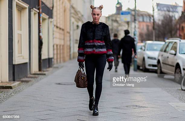 Denise Saidler wearing a fur jacket bun pigtails Louis Vuitton bag skinny black jeans black shoes black gloves on December 29 2016 in Berlin Germany