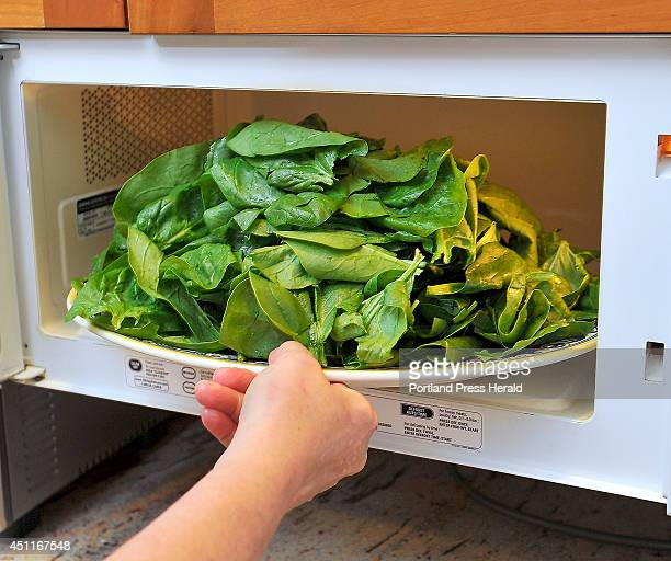 Denise Tepler puts a plate of fresh young spinach from Six Rivers Farm to wilt as she makes grilled burgers using ground lamb and goat meat from a...