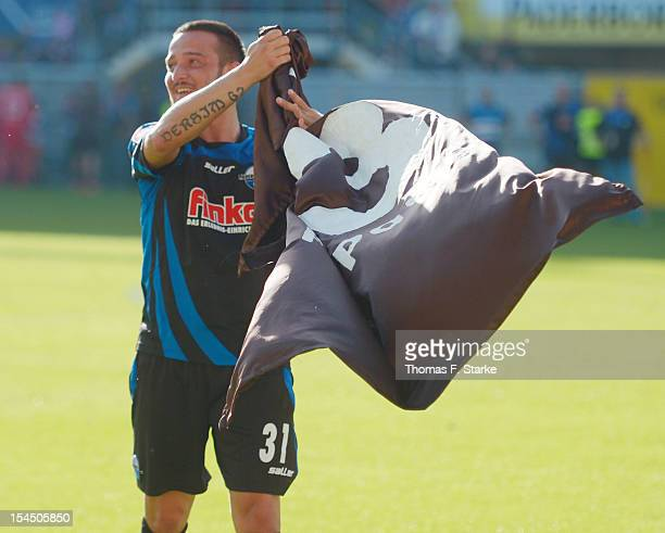 Deniz Naki of Paderborn thanks Sankt Pauli supporters after receiving a oversized shirt with his name after the Second Bundesliga match between SC...