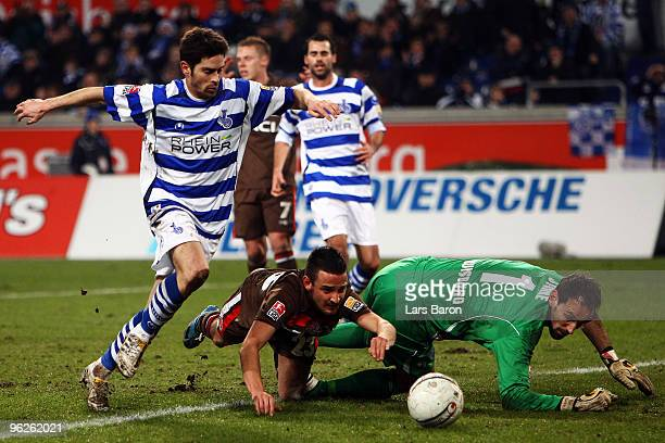 Deniz Naki of St Pauli is challenged by Olivier Veigneau and goalkeeper Tom Starke of Duisburg during the Second Bundesliga match between MSV...