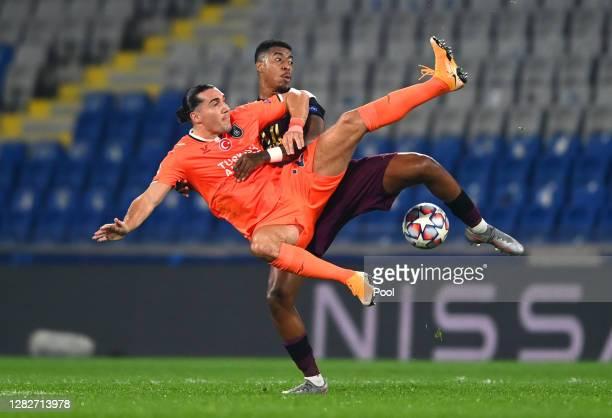 Deniz Turuc of Istanbul Basaksehir FK battles for possession with Presnel Kimpembe of Paris Saint-Germain during the UEFA Champions League Group H...
