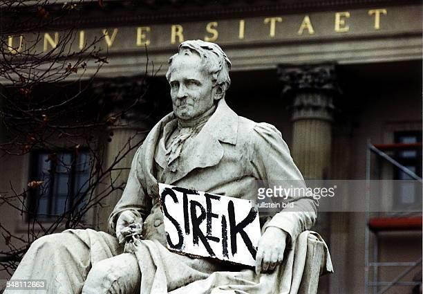 Denkmal Alexander von Humboldt vor der Humboldt-Universität, hält ein handgemaltes Streikschild in der Hand - Dezember 1997