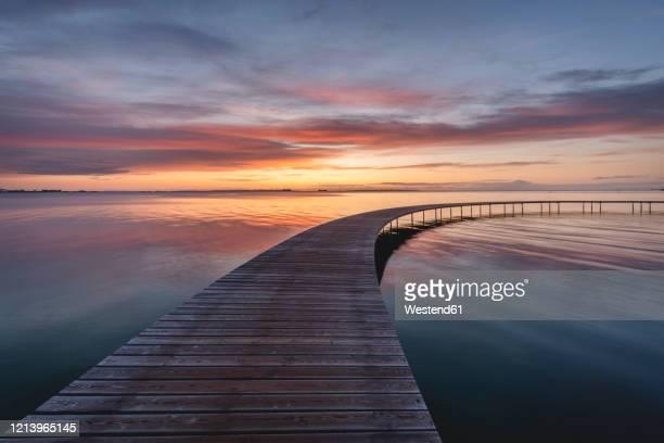 denmark, aarhus, long exposure of infinite bridge and aarhus bay at sunrise - arhus stock pictures, royalty-free photos & images