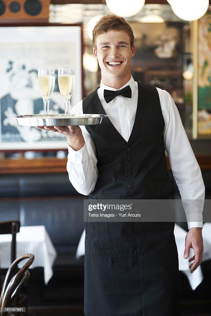 Denmark, Aarhus, Portrait of waiter holding champagne flutes on tray : Stock Photo