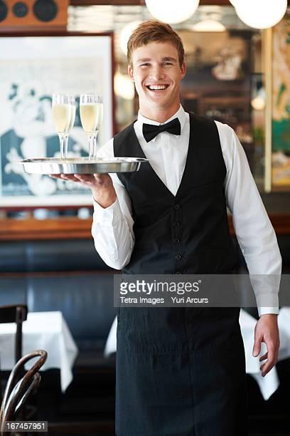 Denmark, Aarhus, Portrait of waiter holding champagne flutes on tray