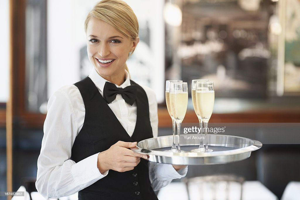 Denmark, Aarhus, Portrait of waitress holding champagne flutes on tray : Stock Photo