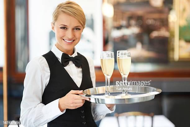 Denmark, Aarhus, Portrait of waitress holding champagne flutes on tray