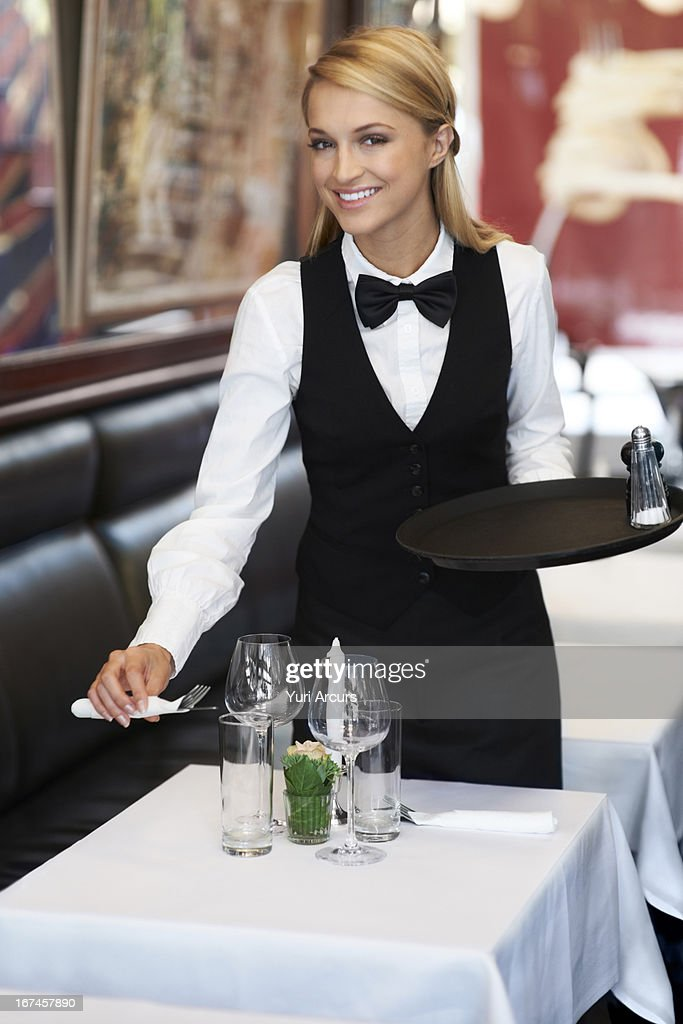 Denmark, Aarhus, Portrait of young waitress setting table : Stock Photo