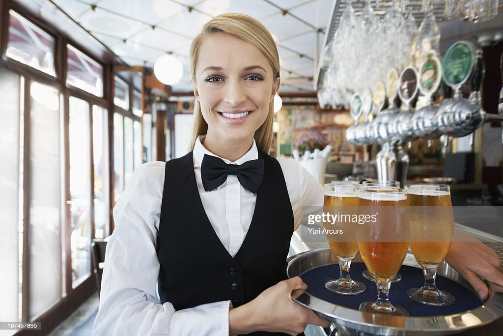 Denmark, Aarhus, Portrait of young woman holding tray with beer glasses : Stock Photo