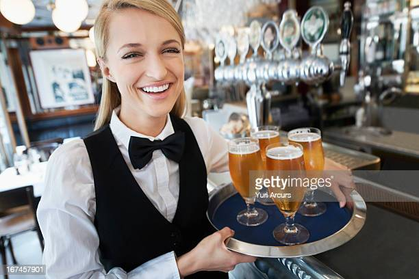 Denmark, Aarhus, Portrait of young woman holding tray with beer glasses