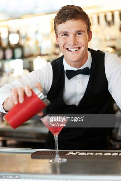 Denmark, Aarhus, Young bartender pouring cocktail