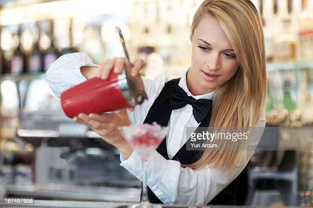 Denmark, Aarhus, Young female bartender pouring cocktail