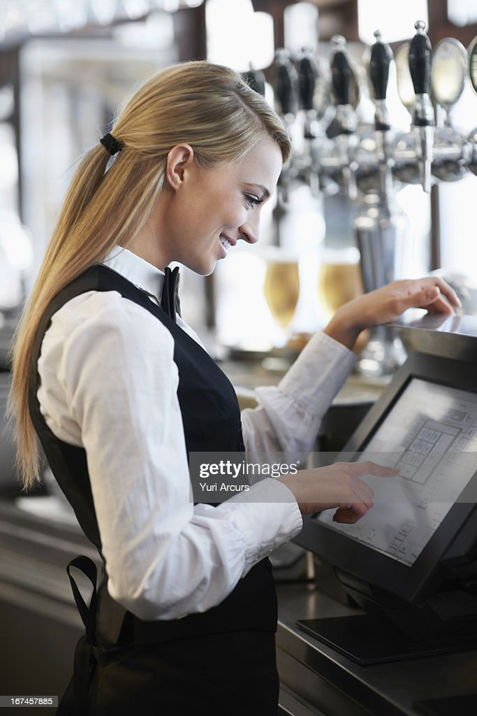 Denmark, Aarhus, Young waitress using computer at restaurant counter : Stock Photo