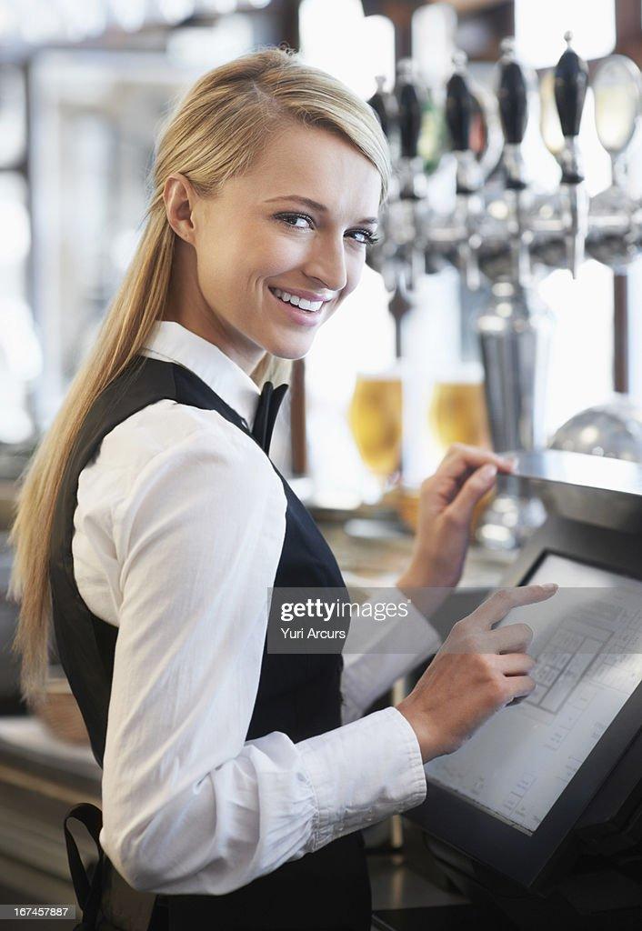 Denmark, Aarhus, Young waitress using computer at restaurant counter : Stock Photo