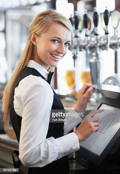 Denmark, Aarhus, Young waitress using computer at restaurant counter