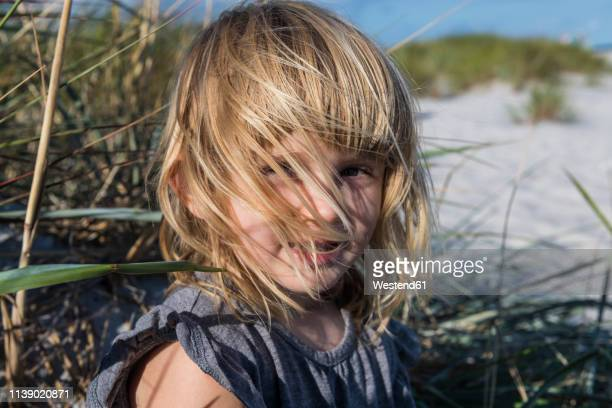 denmark, bornholm, portrait of smiling girl on dueodde white sand beach - ein mädchen allein stock-fotos und bilder