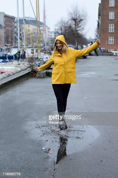 denmark, copenhagen, happy woman jumping in puddles at city harbour - gummistiefel frau stock-fotos und bilder