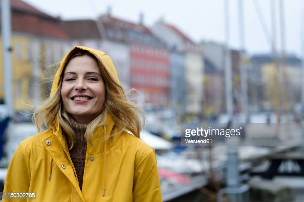 denmark, copenhagen, portrait of happy woman at city harbour in rainy weather - passagier wasserfahrzeug stock-fotos und bilder