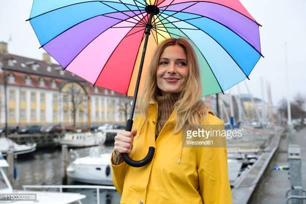 denmark, copenhagen, smiling woman with colourful umbrella at city harbour - solo adulti foto e immagini stock