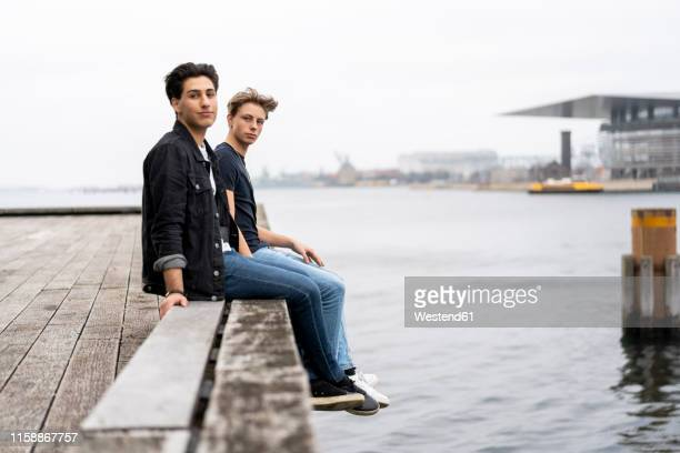 denmark, copenhagen, two young men sitting at the waterfront - denmark stock pictures, royalty-free photos & images