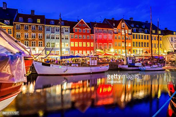 Denmark, Copenhagen, view of historic boats and row of houses at Nyhavn in the evening