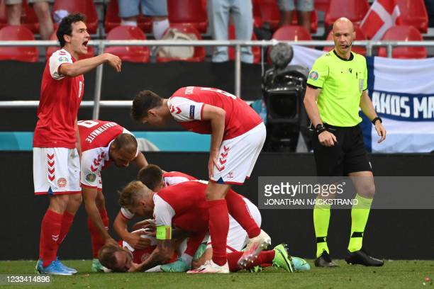 Denmark players help Denmark's midfielder Christian Eriksen after he collapsed during the UEFA EURO 2020 Group B football match between Denmark and...