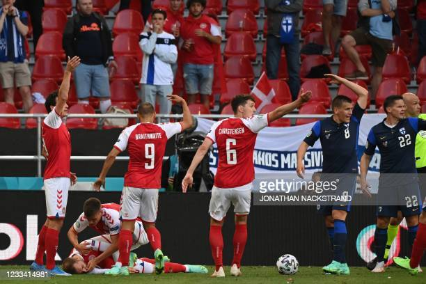 Denmark players help Denmark's midfielder Christian Eriksen as they call for medics after he collapsed during the UEFA EURO 2020 Group B football...