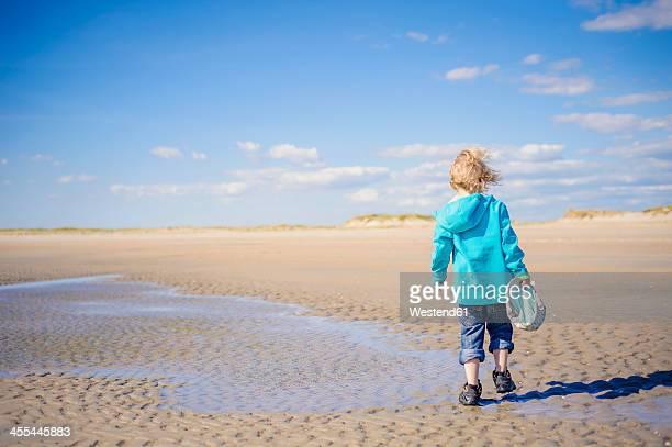 Denmark, Romo, Boy walking at North Sea
