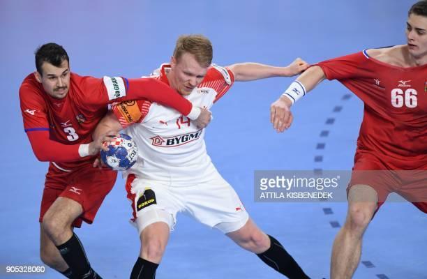 Denmark's Anders Zachariassen fights for the ball with Czech Republic's Roman Becvar and Stepan Zeman during the group D handball match of the Men's...