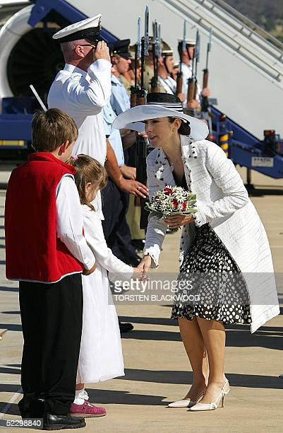 Denmark's Australian-born Crown Princess, Mary Donaldson receives a bouquet of flowers after inspecting the guard-of-honour upon the royal couple's...